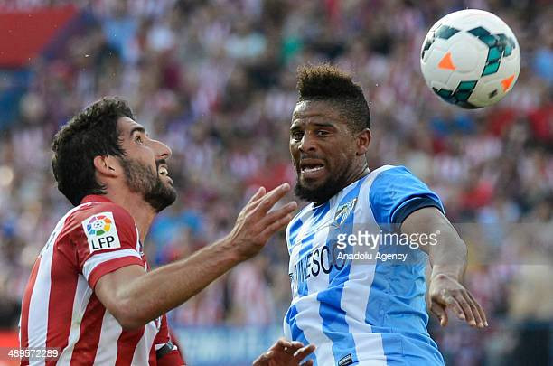 Raul Garcia of Atletico Madrid in action against his rival of Malaga under La Liga at Vicente Calderon in Madrid May 11 2014