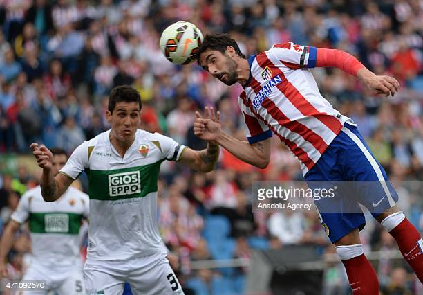Raul Garcia of Atletico Madrid is in action against Roco of Elche during La Liga match between Club Atletico de Madrid and Elche at Vicente Calderon...