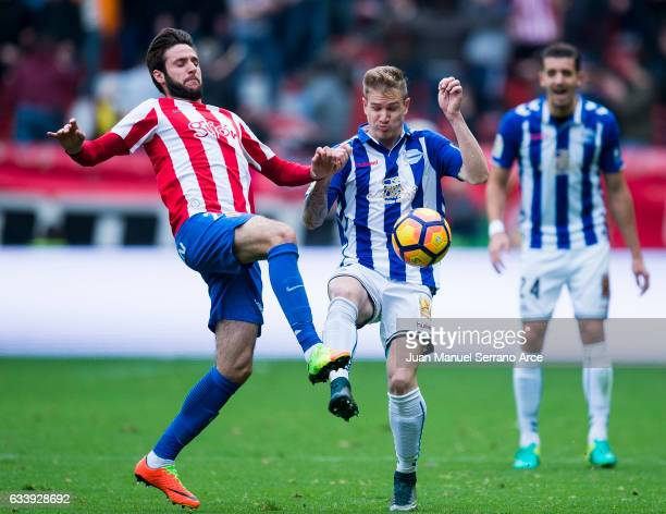 Raul Garcia of Deportivo Alaves duels for the ball with Duje Cop of Real Sporting de Gijon during the La Liga match between Real Sporting de Gijon...