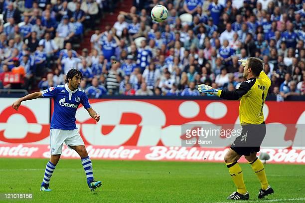 Raul Gonzalez of Schalke scores his teams fourth goal over goalkeeper Michael Rensing of Koeln during the Bundesliga match between FC Schalke 04 and...