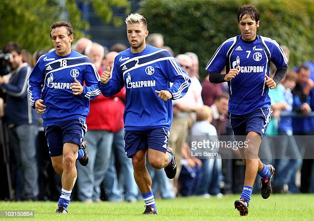 Raul Gonzalez runs with team mates Rafinha and Vassilios Pliatsikas during a FC Schalke 04 training session at the training ground on July 29 2010 in...