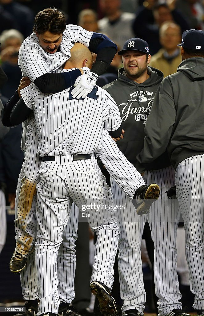 <a gi-track='captionPersonalityLinkClicked' href=/galleries/search?phrase=Raul+Ibanez&family=editorial&specificpeople=206118 ng-click='$event.stopPropagation()'>Raul Ibanez</a> #27 of the New York Yankees celebrates a walk off home run in the bottom of the twelfth inning with teammate <a gi-track='captionPersonalityLinkClicked' href=/galleries/search?phrase=Nick+Swisher&family=editorial&specificpeople=206417 ng-click='$event.stopPropagation()'>Nick Swisher</a> #33 after defeating the Baltimore Orioles in Game Three of the American League Division Series at Yankee Stadium on October 10, 2012 in the Bronx borough of New York City.