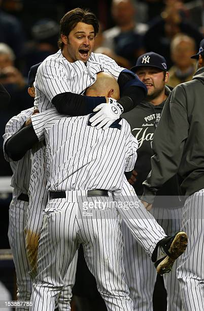 Raul Ibanez of the New York Yankees celebrates a walk off home run in the bottom of the twelfth inning with teammate Nick Swisher after defeating the...