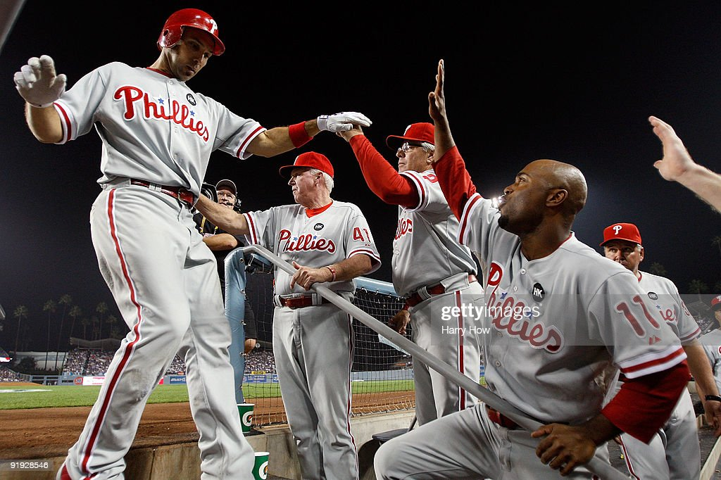 <a gi-track='captionPersonalityLinkClicked' href=/galleries/search?phrase=Raul+Ibanez&family=editorial&specificpeople=206118 ng-click='$event.stopPropagation()'>Raul Ibanez</a> #29 of the Philadelphia Phillies get congratulated by his teammates including, <a gi-track='captionPersonalityLinkClicked' href=/galleries/search?phrase=Jimmy+Rollins&family=editorial&specificpeople=204478 ng-click='$event.stopPropagation()'>Jimmy Rollins</a> #11, as he enters the dugout after hitting a three run home run in the eighth inning in Game One of the NLCS off of pitcher George Sherrill (not pictured) of the Los Angeles Dodgers during the 2009 MLB Playoffs at Dodger Stadium on October 15, 2009 in Los Angeles, California.