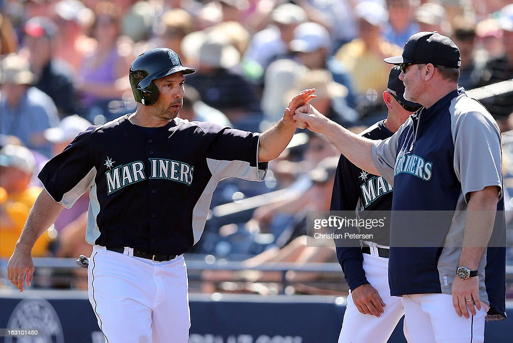 Raul Ibanez #28 of the Seattle Mariners high-fives manager Eric Wedge after Ibanez scored a first inning run against the Colorado Rockies during the spring training game at Peoria Stadium on March 4, 2013 in Peoria, Arizona.