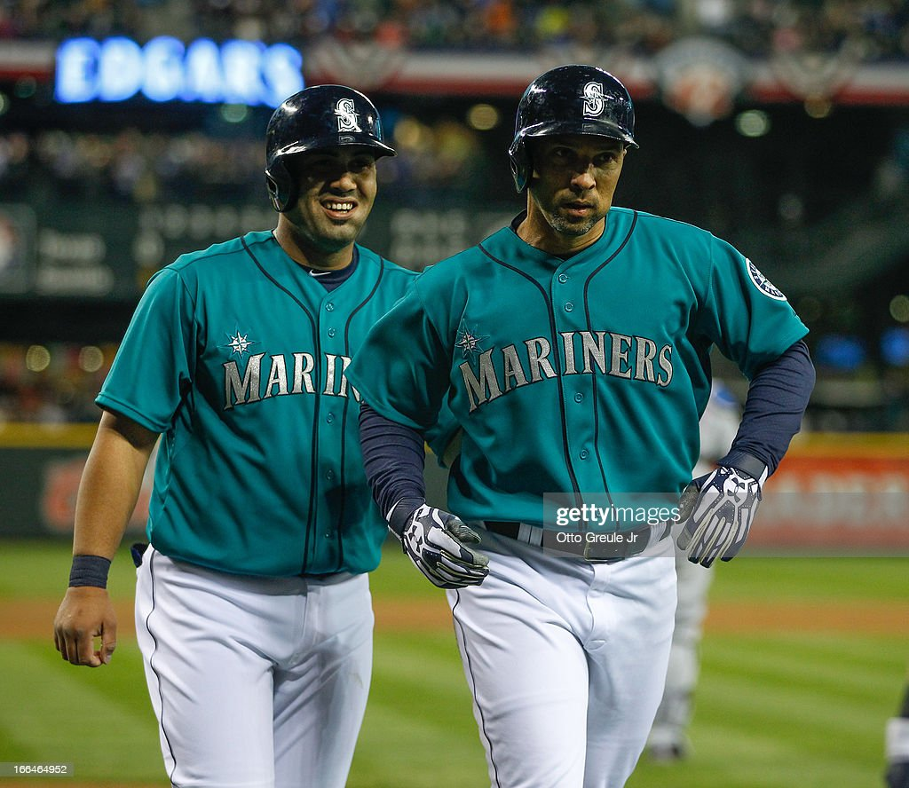 <a gi-track='captionPersonalityLinkClicked' href=/galleries/search?phrase=Raul+Ibanez&family=editorial&specificpeople=206118 ng-click='$event.stopPropagation()'>Raul Ibanez</a> #28 (R) of the Seattle Mariners is congratulated by <a gi-track='captionPersonalityLinkClicked' href=/galleries/search?phrase=Jesus+Montero&family=editorial&specificpeople=4900196 ng-click='$event.stopPropagation()'>Jesus Montero</a> #63 after scoring on a two-run double by Kyle Seager in the first inning against the Texas Rangers at Safeco Field on April 12, 2013 in Seattle, Washington.