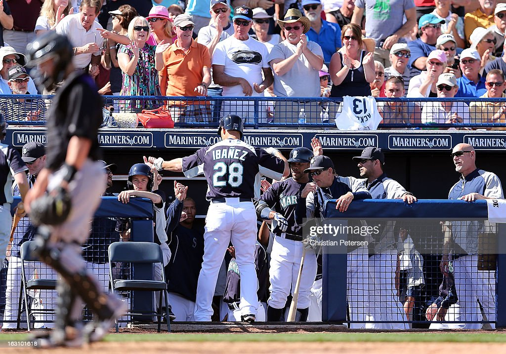 <a gi-track='captionPersonalityLinkClicked' href=/galleries/search?phrase=Raul+Ibanez&family=editorial&specificpeople=206118 ng-click='$event.stopPropagation()'>Raul Ibanez</a> #28 of the Seattle Mariners is congratulated by teammates in the dugout after hitting a solo home run against the Colorado Rockies during the third inning of the spring training game at Peoria Stadium on March 4, 2013 in Peoria, Arizona.