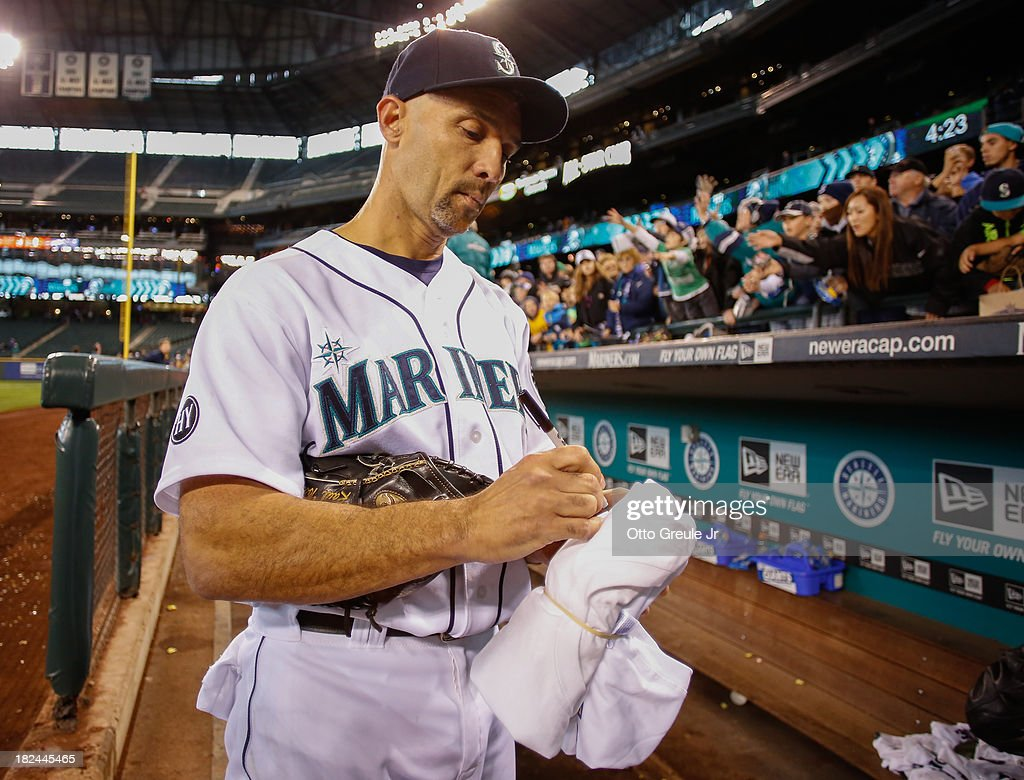 Raul Ibanez #28 of the Seattle Mariners signs autographs for fans after the final game of the regular season against the Oakland Athletics at Safeco Field on September 29, 2013 in Seattle, Washington. The Athletics defeated the Mariners 9-0.