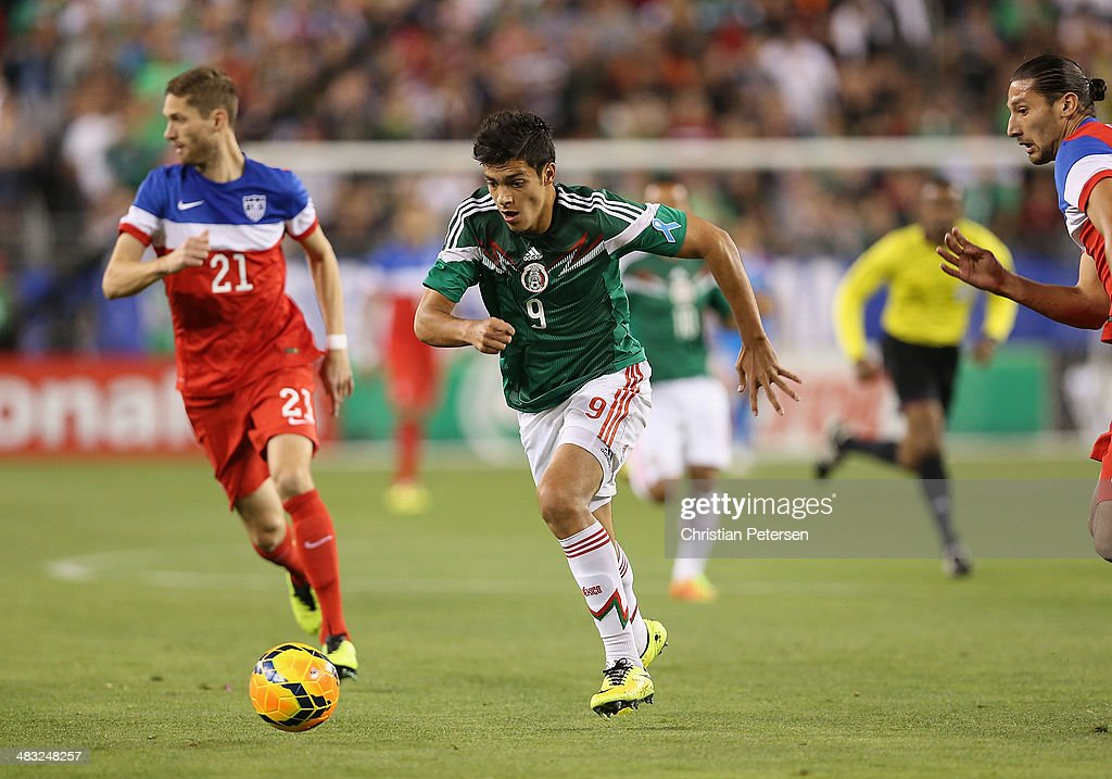 Raul Jimenez of Mexico controls the ball past Clarence Goodson of USA during the International Friendly at University of Phoenix Stadium on April 2...