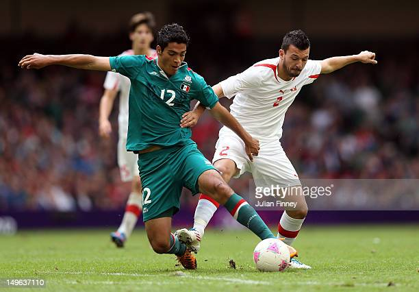 Raul Jimnenz Rodriguez of Mexico battles with Xavier Hochstrasser of Switzerland during the Men's Football first round Group B match between Mexico...