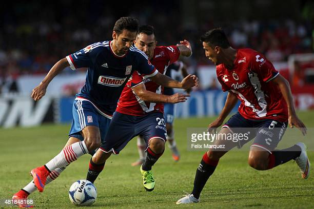 Raul Lopez of Chivas drives the ball as he faces the mark of Darvin Chavez of Veracruz during a 1st round match between Veracruz and Chivas as part...