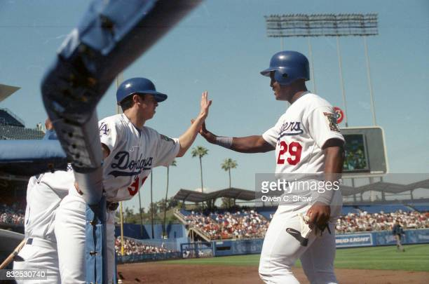 Raul Mondesi of the Los Angeles Dodgers id congratulated by the bat boy after hitting a home run at Dodger Stadium circa 1999 in Los Angeles...