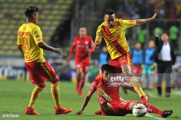 Raul Ruidiaz and Gerardo Rodriguez of Morelia vie for the ball with Pablo Barrientos of Toluca during their quarter final Mexican Apertura tournament...