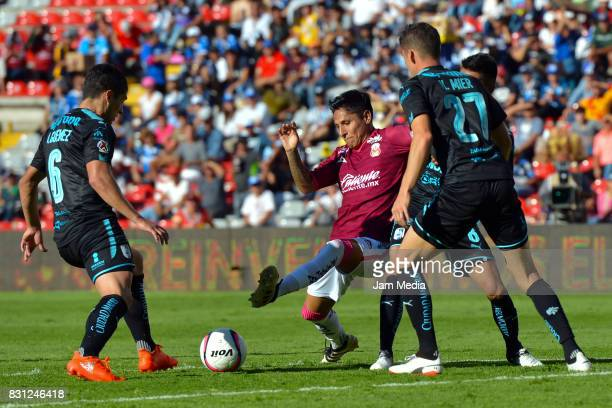 Raul Ruidiaz of Morelia competes for the ball with Javier Guemez and Hiram Mier of Queretaro during the 4th round match between Queretaro and Morelia...