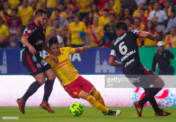 Raul Ruidiaz of Morelia vies for the ball with Hiram Munoz and Juan Valenzuela of Tijuana during their Mexican Clausura 2017 Tournament first leg...