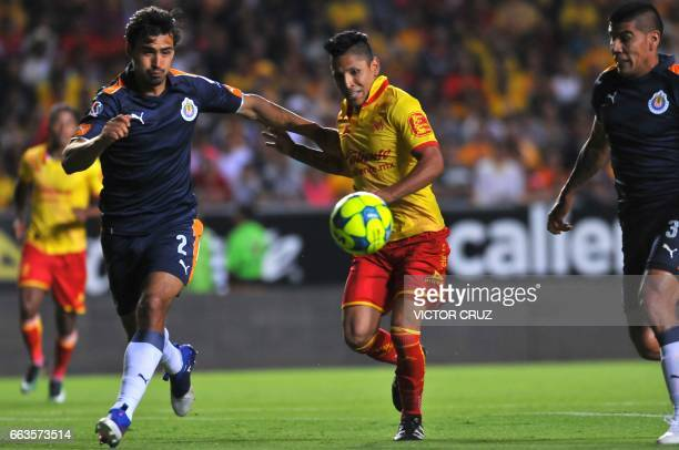 Raul Ruidiaz of Morelia vies for the ball with Oswaldo Alanis and Carlos Salcido of Guadalajara during their Mexican Clausura 2017 Tournament...