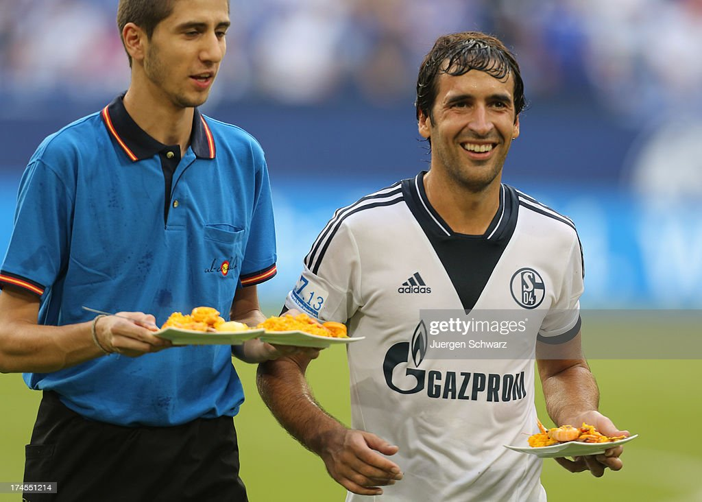 Raul (R) serves Spanish food to team-mates after his farewell match between Schalke 04 and Al-Sadd Sports Club Katar at Veltins Arena on July 27, 2013 in Gelsenkirchen, Germany.