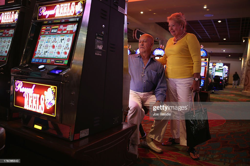 Raul Suarez (L) and Mercy Suarez enjoy playing a slot machine in the casino that will hold its grand opening on Friday located in the Hialeah Park Race Track which first opened in 1925 on August 28, 2013 in Hialeah, Florida. The new casino is located in the same complex as the race track which in its heyday was known as the 'the worlds most beautiful race course.'
