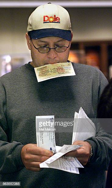 Raul Valencia of Thousand Oaks waits in line with check in mouth to pay his property tax at the Government Center in Ventura on Monday morning The...