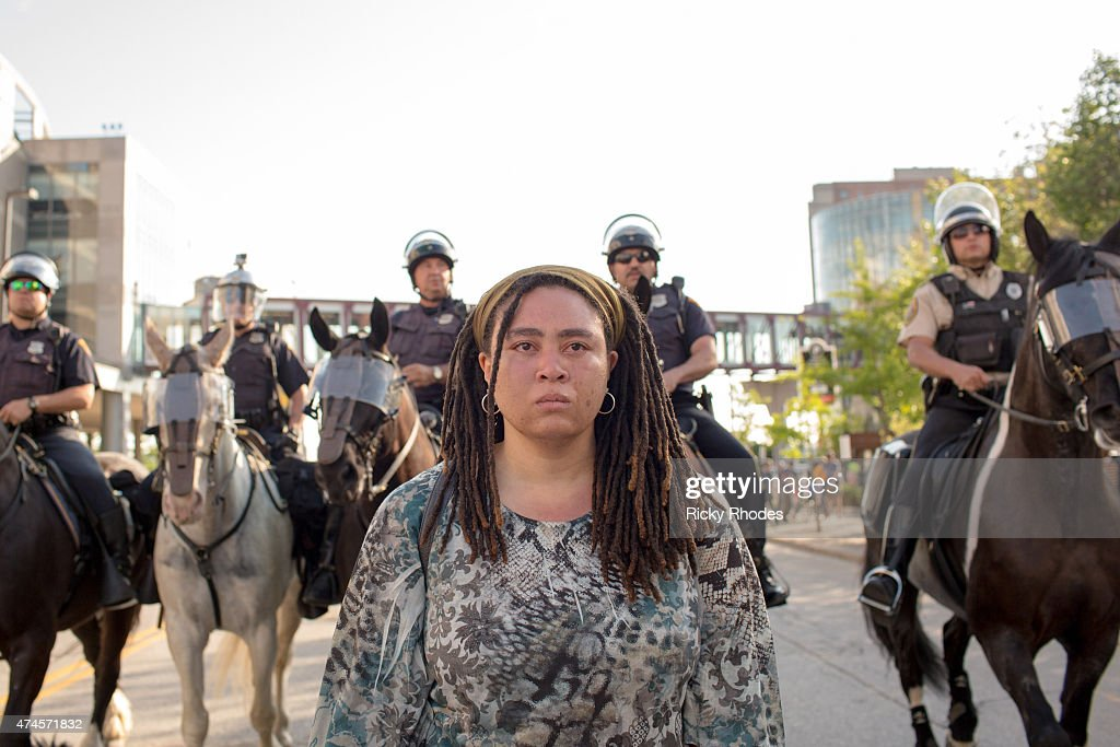 Raven Evans walks outside of the Q Arena after police pepper sprayed her during protests in reaction to Cleveland police officer Michael Brelo being...
