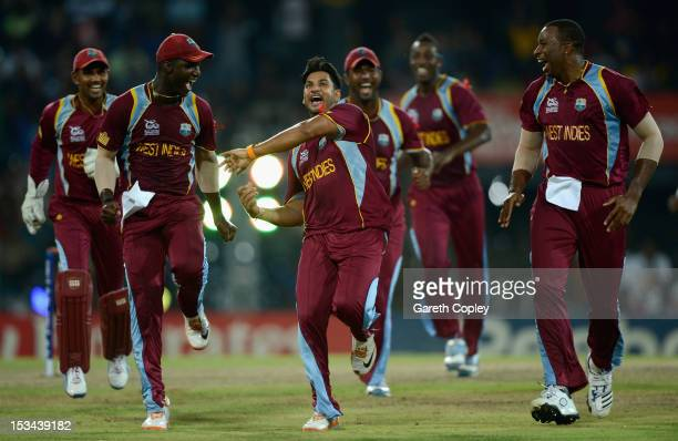 Ravi Rampaul of the West Indies celebrates with Darren Sammy and Kieron Pollard after dismissing David Hussey of Australia during the ICC World...