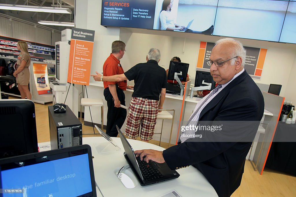 Ravi Saligram, president and chief executive officer of OfficeMax Inc., views a laptop on display inside the company's new Business Solutions Center in Chicago, Illinois, U.S., on Tuesday, Aug. 27, 2013. The OfficeMax Business Solutions Center provides local businesses with services including designed marketing, web, document, IT and shipping service. Photographer: Tim Boyle/Bloomberg via Getty Images