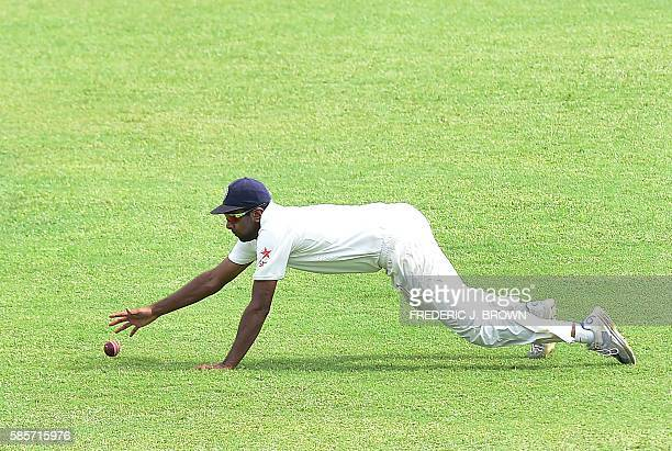 Ravichandran Ashwin dives but misses stopping the ball hit by Roston Chase of the West Indies off a delivery from bolwer Mohammed Shami on day five...