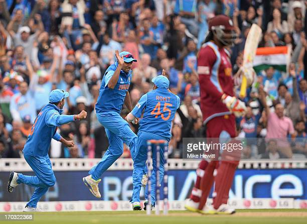 Ravichandran Ashwin of India celebrates with Rohit Sharma after taking the catch to dismiss Chris Gayle of the West Indies during the ICC Champions...