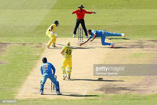 Ravichandran Ashwin of India fields his own delivery after Steve Smith of Australia plays a shot during the 2015 Cricket World Cup Semi Final match...