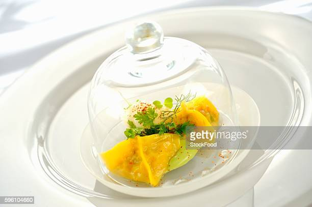 Ravioli filled with king crab under a glass cloche on a glass plate