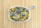 Top view of a cooked spinach ravioli TV dinner with vegetables in a microwavable tray plus a fork in the food atop a wood place mat.