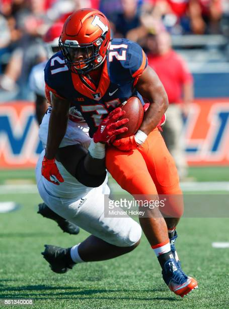 Ra'Von Bonner of the Illinois Fighting Illini runs the ball as Kevin Wilkins of the Rutgers Scarlet Knights makes the tackle behind the line of...