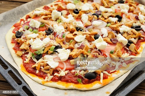 Raw al funghi pizza with chanterelle mushrooms and olives : Stock Photo