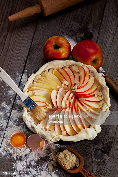 Raw apple pie in cake pan and ingredients on wood