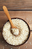 Raw uncooked basmati rice in wooden bowl. Top view with copy space
