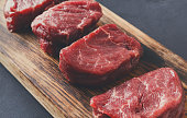 Raw filet mignon steaks. Slices of fresh beef meat arranged in a row on wooden cutting board at gray background with copy space. Organic ingredients for restaurant meals, meat texture closeup
