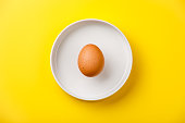 Raw brown chicken Egg in bowl on yellow background