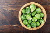 raw brussels sprouts in a plate on a wooden background, space for text