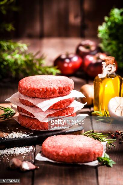 Raw burger patties on rustic wooden table