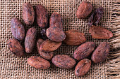Raw cacao beans on a burlap cloth background. Top view, close up