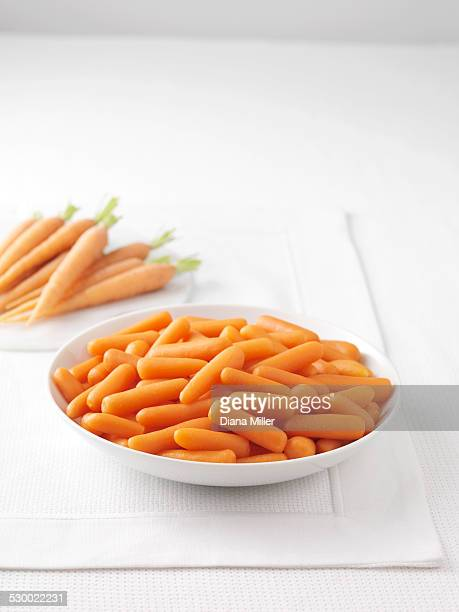 Raw carrots on marble cutting board and bowl of boiled carrots