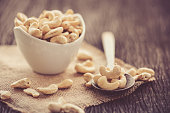 raw cashew nuts in white ceramic bowl on wood table,vintage tone