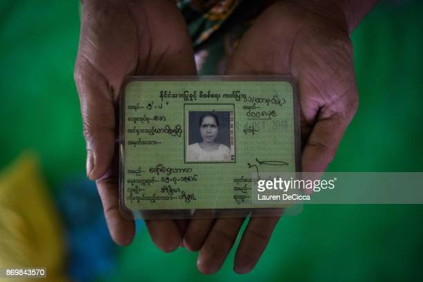 Raw Chabarla holds her green identification card the only item that she was able to save before her home in Myanmar's Maungdaw township was burnt in...