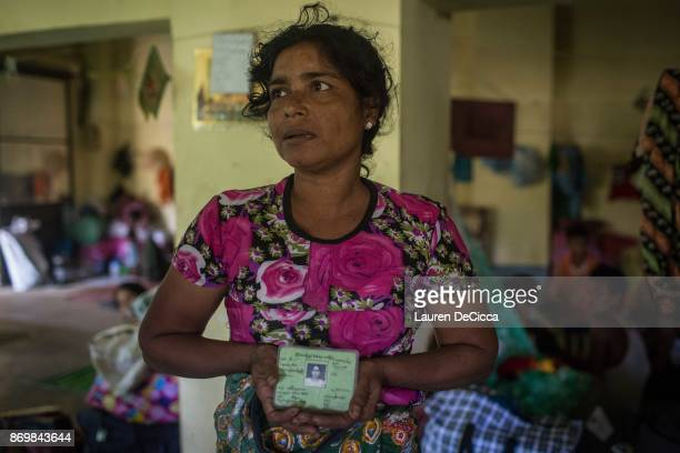 Raw Chabarla holds her green identification card the only item that she was able to save before her home in Myanmar's Maungdaw township was burned in...