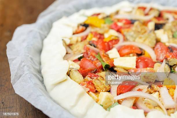 生のチーズと野菜のピザパイを焼く紙