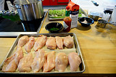 Raw chicken and asparagus sit on trays after being prepped for a meal during a cooking class at The Seasoned Chef Cooking School on July 19 2016