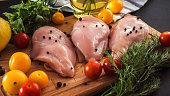 Raw chicken breast fillets and vegetable on wooden background