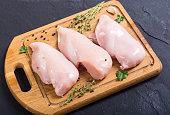 Raw chicken breast with spices on cutting board