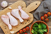 Raw chicken drumstick on a cutting board, cherry tomatoes, spinach, garlic, towel on a wooden table, top view