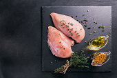 Raw chicken fillets on black cutting board with spices and herbs. Cooking ingredients. Natural healthy food concept. Flat lay with space for text